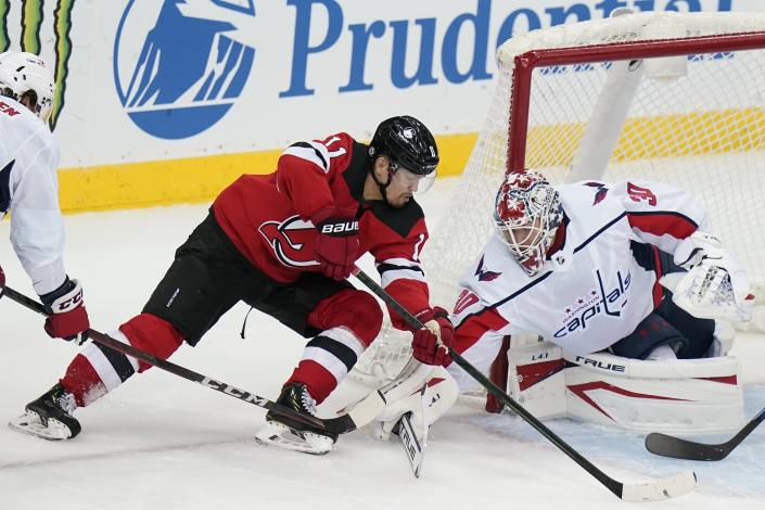 Washington Capitals goaltender Ilya Samsonov (30) stops a shot on goal by New Jersey Devils' Andreas Johnsson (11) during the first period of an NHL hockey game Sunday, April 4, 2021, in Newark, N.J. (AP Photo/Frank Franklin II)