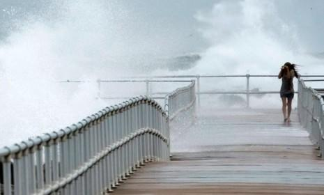A woman walks along a jetty in Ponce Inlet, Fla., on Oct. 26: Hurricane Sandy and the oncoming Frankenstorm may be the election's real October surprise.