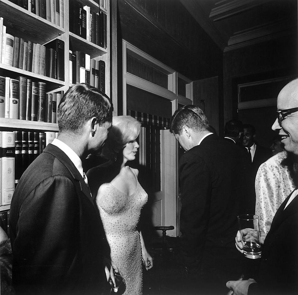 At a party, Marilyn Monroe stands between Robert Kennedy (left) and John F. Kennedy, New York, New York, May 19, 1962.