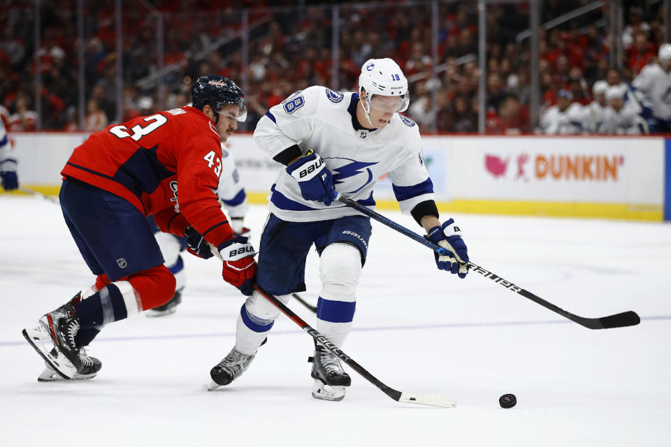 Tampa Bay Lightning left wing Ondrej Palat, right, of the Czech Republic, stakes with the puck past Washington Capitals right wing Tom Wilson during the third period of an NHL hockey game Friday, Nov. 29, 2019, in Washington. Washington won 4-3 in overtime. (AP Photo/Patrick Semansky)