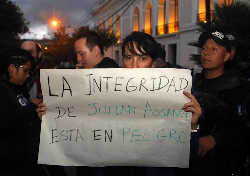 "A protester outside the Foreign Ministry in Quito, Ecuador holds a placard reading ""Assange's Safety is in Danger,"" after British police took WikiLeaks founder Julian Assange out of Ecuador's embassy in London and arrested him"