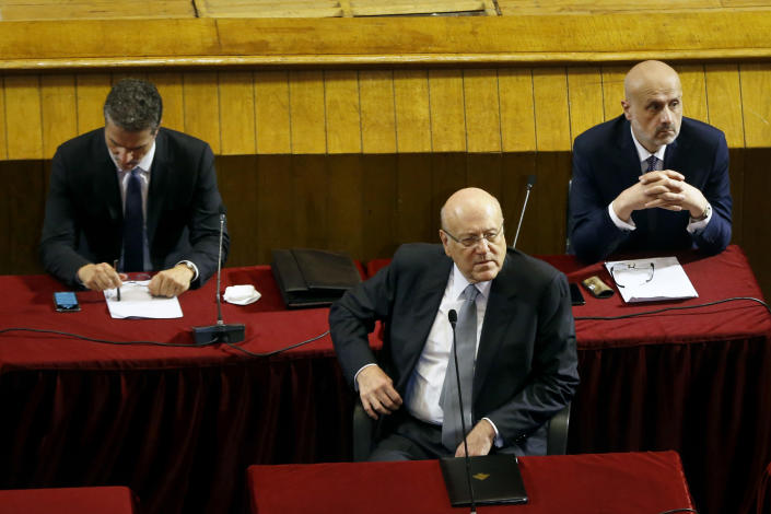 Lebanese Prime Minister Najib Mikati, center, attends a parliament session to confirm Lebanon's new government at a Beirut theater known as the UNESCO palace so that parliament members could observe social distancing measures imposed over the coronavirus pandemic, Lebanon, Monday, Sept. 20, 2021. A power outage and a broken generator briefly delayed the start of the parliament session for some 40 minutes before electricity came back on. (AP Photo/Bilal Hussein)