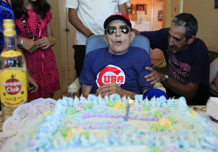 FILE - In this April 25, 2013 file photo, Conrado Marrero, the oldest living former Major League Baseball player, is surrounded by family and friends as he blows out the candle on his birthday cake at his home in Havana, Cuba. Family members say Conrado Marrero has died in Havana. He was 102, just two days short of his 103rd birthday. Grandson Rogelio Marrero confirmed the death Wednesday afternoon, April 23, 2014. (AP Photo/Franklin Reyes, File)
