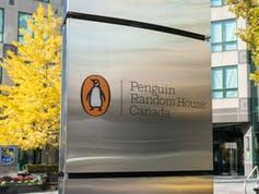 Logo of a penguin at Penguin Random House Canada office on a silver post outdoors.