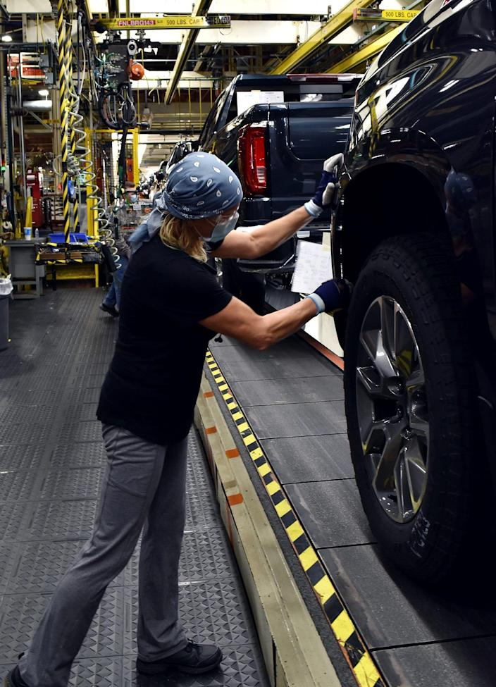 A worker wears a face mask while building GM's full-sized pickups at Fort Wayne Assembly plant in Indiana. Jan. 7, 2021.