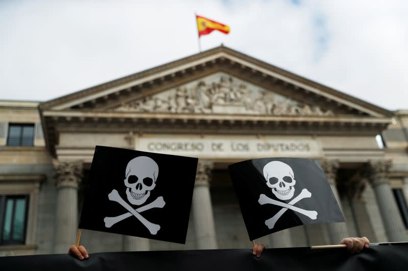 People who protest against a law to legalise euthanasia as Spanish Parliament prepares to vote on it, hold placards with skulls outside the Spanish Parliament in Madrid