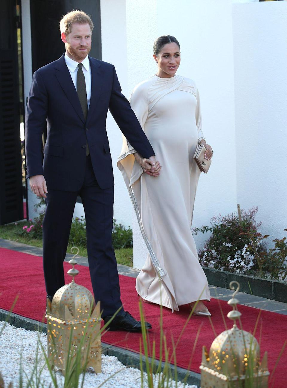 """<p>Last year, Meghan and Prince Harry toured Morocco and attended a reception hosted by the British Ambassador. For this event, Meghan, pregnant at the time, stunned in a cream, <a href=""""https://www.townandcountrymag.com/style/fashion-trends/a26496908/meghan-markle-cream-bespoke-dior-dress-morocco-photos/"""" rel=""""nofollow noopener"""" target=""""_blank"""" data-ylk=""""slk:bespoke Dior cape dress"""" class=""""link rapid-noclick-resp"""">bespoke Dior cape dress</a>. <br></p>"""