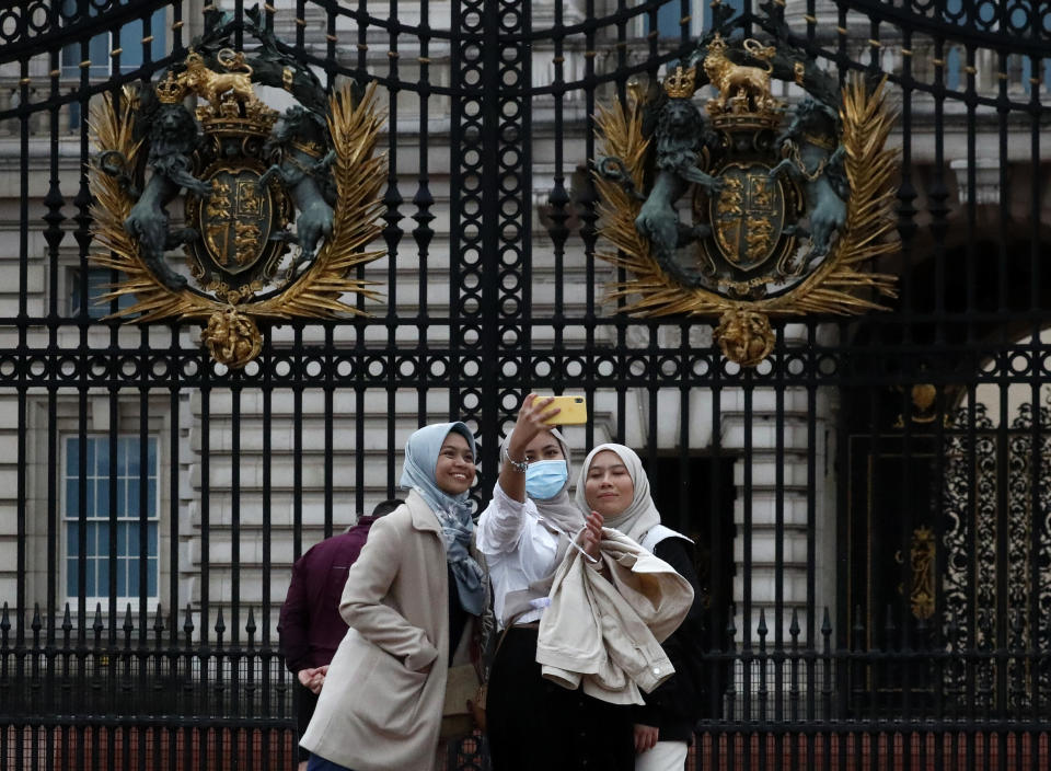 """Tourists pose for selfies in front of the gates of Buckingham Palace in London, Monday, April 5, 2021. The British government says all asymptomatic people in England will be able to get two free coronavirus tests per week, starting Friday, as a way to stamp out new outbreaks, and Prime Minister Boris Johnson said that regular testing would help """"stop outbreaks in their tracks."""" (AP Photo/Frank Augstein)"""