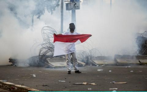 A student holds an Indonesian flag at a rally outside the parliament - Credit: Getty Images/Oscar Siagian