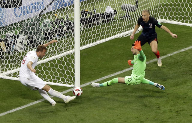 Croatia goalkeeper Danijel Subasic saves a shot from England's Harry Kane, left, during the semifinal match between Croatia and England at the 2018 soccer World Cup in the Luzhniki Stadium in Moscow, Russia, Wednesday, July 11, 2018. (AP Photo/Thanassis Stavrakis)