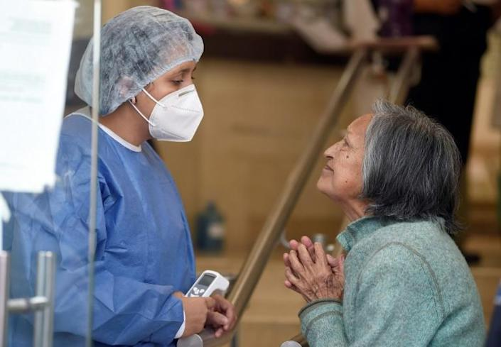 A nurse listens to the relative of patient hospitalized at the Tacuba General Hospital in Mexico City (AFP Photo/ALFREDO ESTRELLA)