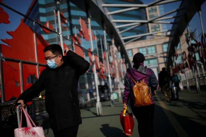A man wearing a face mask pushes his luggage at a footbridge near Beijing Railway Station as the country is hit by an outbreak of the new coronavirus, in Beijing