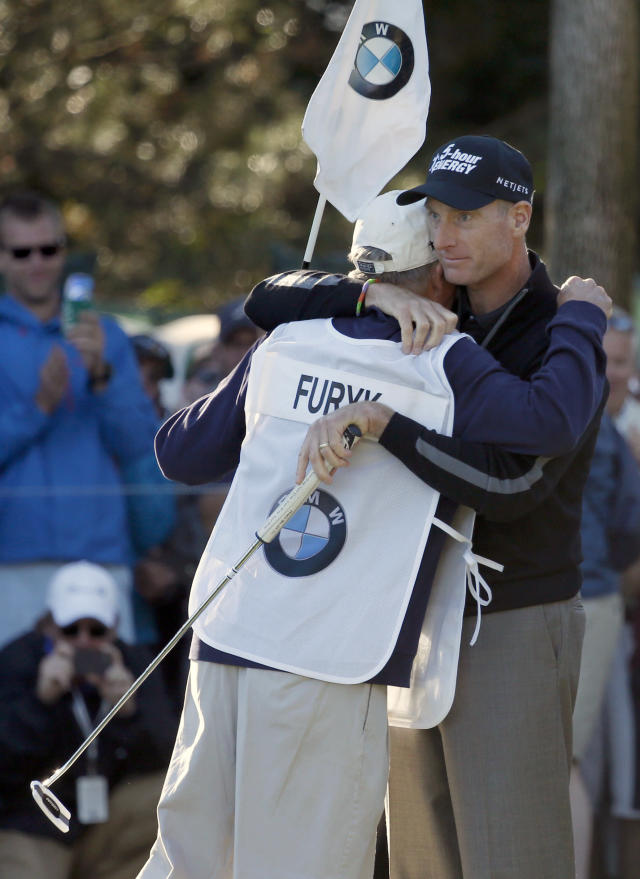 Jim Furyk, right, hugs his caddie Mike Cowan after posting a 59, becoming sixth player to reach that milestone, during the second round of the BMW Championship golf tournament at Conway Farms Golf Club in Lake Forest, Ill., Friday, Sept. 13, 2013. (AP Photo/Charles Rex Arbogast)