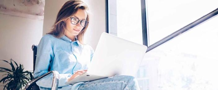 Woman using Laptop in huge Loft Studio to research refinance mortgage rates.