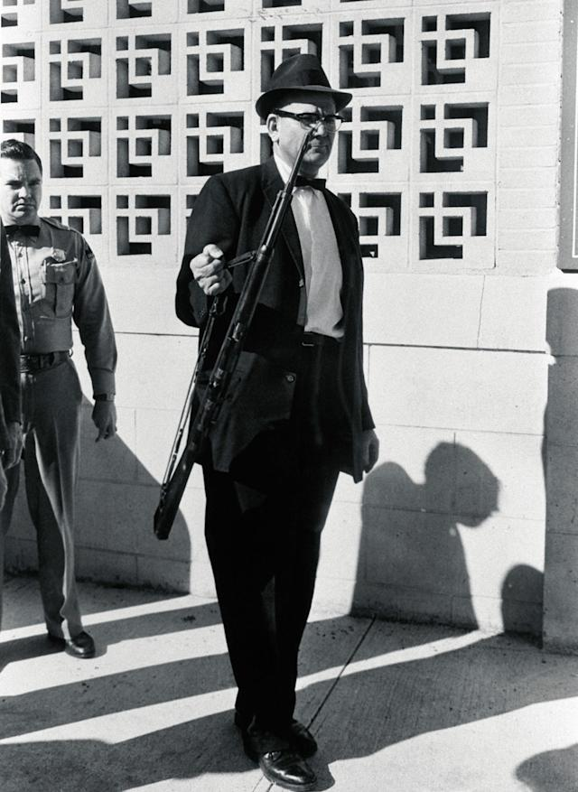 <p>An investigator removes from the Texas School Book Depository the rifle allegedly used to assassinate President Kennedy. (Photo: Corbis via Getty Images) </p>