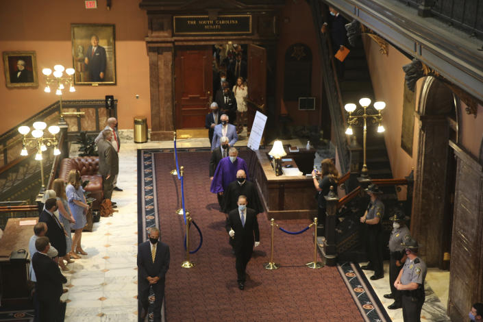 South Carolina senators walk across the Statehouse lobby for a joint session with the House on Wednesday, May 5, 2021, in Columbia, S.C. Senators sat in the balcony for the joint session because of COVID-19 concerns. (AP Photo/Jeffrey Collins)