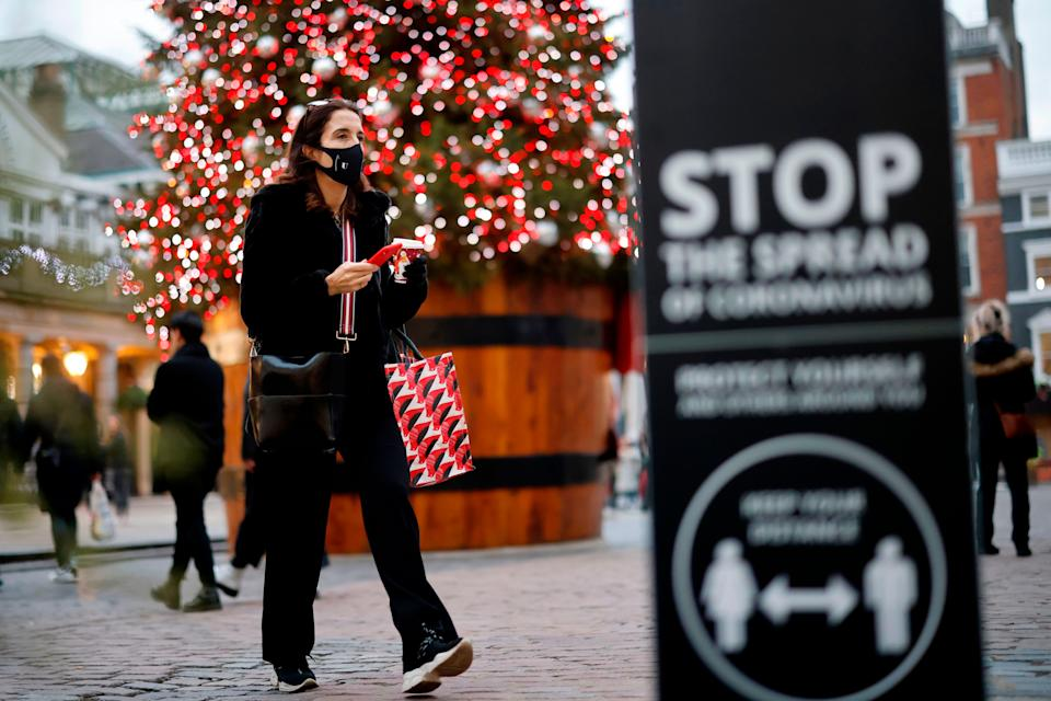 A pedestrian wearing a protective face covering walks past the Christmas tree in Covent Garden in central London on November 27 (Photo: TOLGA AKMEN via Getty Images)