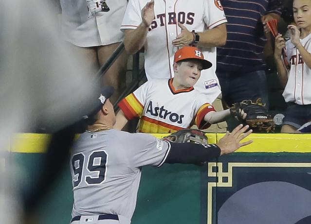 A young fan catches a home run hit by Houston Astros' Carlos Correa in front of New York Yankees' Aaron Judge (99) during the fourth inning of Game 2 of baseball's American League Championship Series Saturday, Oct. 14, 2017, in Houston. (AP)