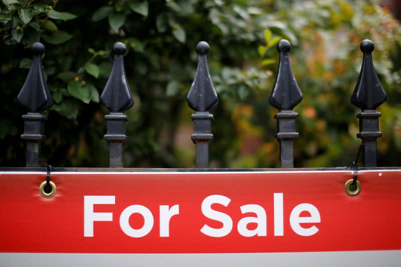 FILE PHOTO: A real estate sign is seen hanging on a fence in front of a house for sale in Ottawa