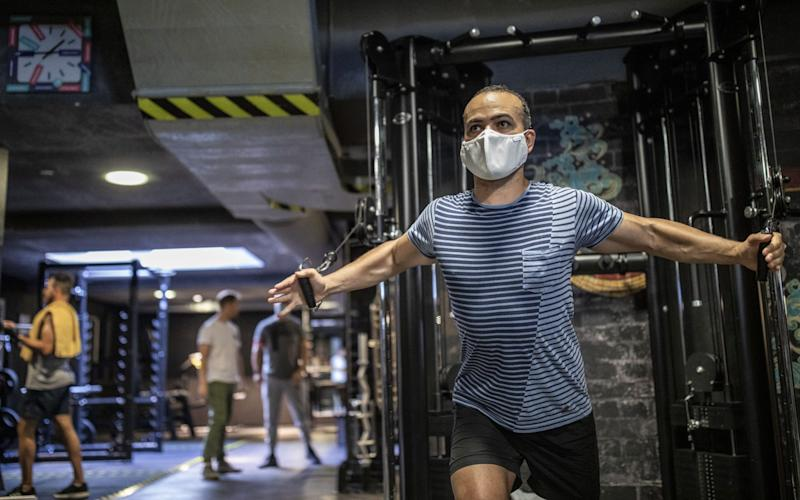 Man performs exercise while wearing facemask in gym - GETTY IMAGES