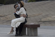 A couple wearing masks sit together on a bench as the city of Wuhan slowly loosen up ahead of a lifting of the two months long lockdown in central China's Hubei province on Sunday, April 5, 2020. The quarantine in the city which is the epicenter of China's coronavirus outbreak is to be formally lifted on Wednesday. (AP Photo/Ng Han Guan)