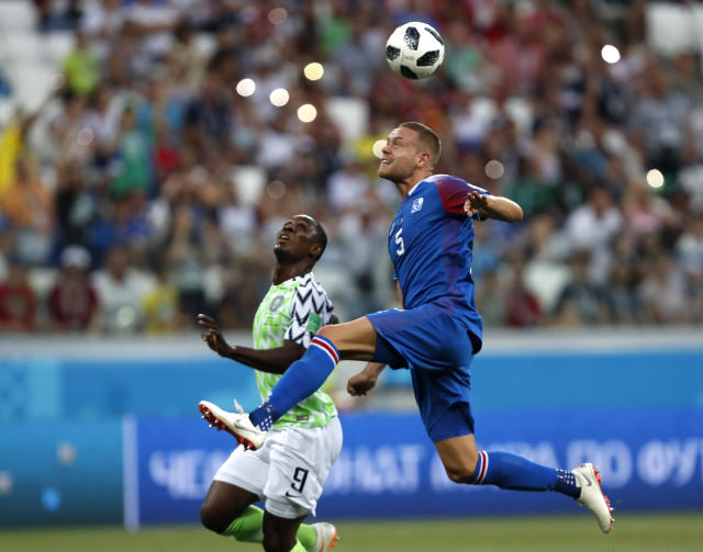 Iceland's Sverrir Ingason, right, leaps as he heads the ball clear of Nigeria's Odion Ighalo the group D match between Nigeria and Iceland at the 2018 soccer World Cup in the Volgograd Arena in Volgograd, Russia, Friday, June 22, 2018. (AP Photo/Darko Vojinovic)