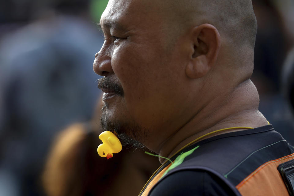 CORRECTS PHOTOGRAPHER'S NAME - A protester adorns his beard with a yellow duck, which has become a good-humored symbol of resistance during anti-government rallies, Friday, Nov. 27, 2020 in Bangkok, Thailand. Pro-democracy demonstrators are continuing their protests calling for the government to step down and reforms to the constitution and the monarchy, despite legal charges being filed against them and the possibility of violence from their opponents or a military crackdown. (AP Photo/WasonWanichakorn)