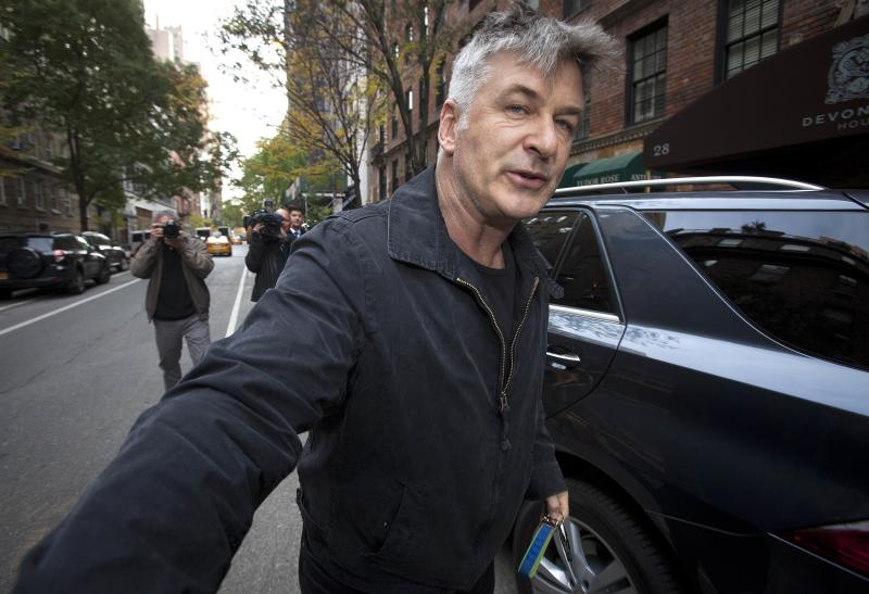 Actor Alec Baldwin shoves a photographer and tells him to move out of his way after he arrived in his SUV at the building where he lives in New York