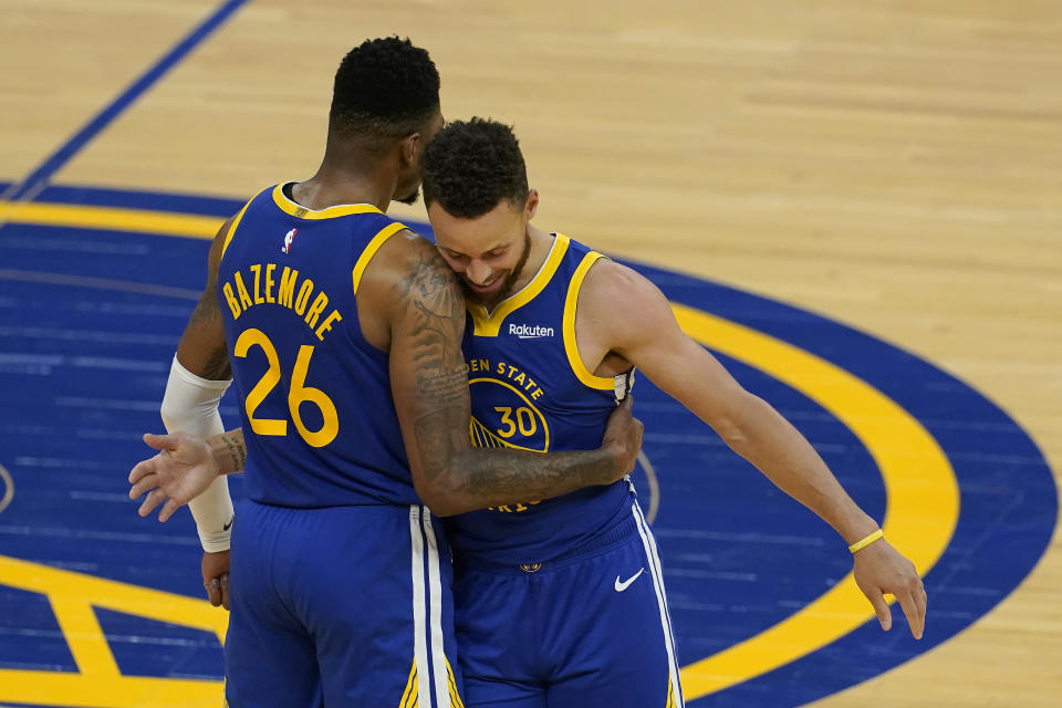 Golden State Warriors forward Kent Bazemore (26) is congratulated by guard Stephen Curry (30) after scoring against the Denver Nuggets during the second half of an NBA basketball game in San Francisco, Monday, April 12, 2021. (AP Photo/Jeff Chiu)