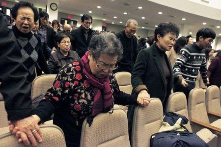 Participants hold hands together as they pray for Canadian pastor Hyeon Soo Lim who is being held in North Korea during a joint multi-cultural prayer meeting at Light Korean Presbyterian Church in Toronto, December 20, 2015. REUTERS/Hyungwon Kang