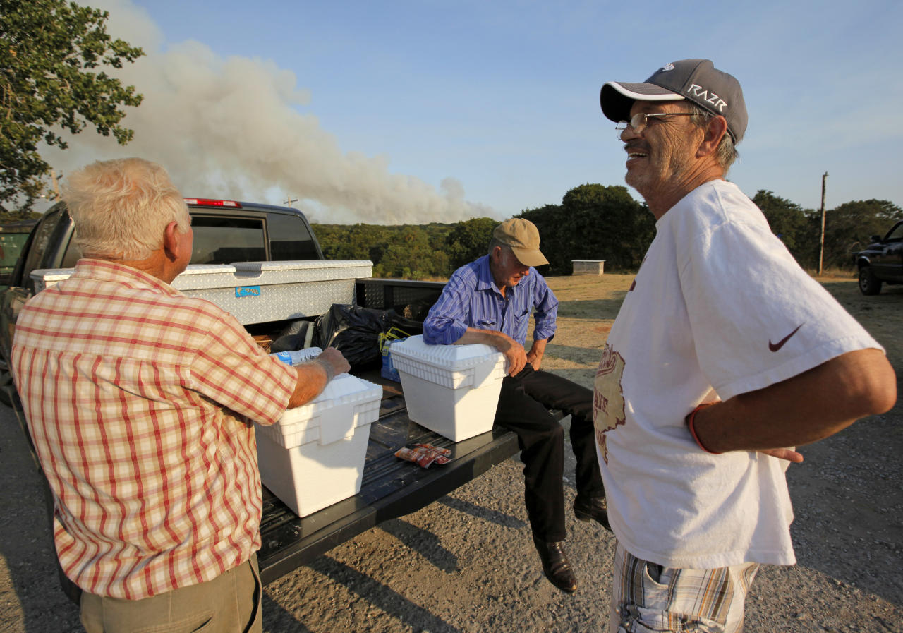 From left, Gayland Cannon, Eugene Hacker and Ron Ross wait at a gas station at SE108 and Hwy 9 after evacuating their homes in the area of SE 132nd and Cedar Lane as a wildfire burns through Cleveland County near Norman, Okla., Friday, Aug. 3, 2012. A wildfire stirred by high winds sweeping through rural woodlands just south of the Oklahoma City area has set at a number of homes on fire. (AP Photo/The Oklahoman, Nate Billings) TABLOIDS OUT