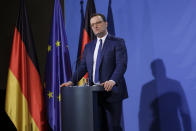German Health Minister Jens Spahn briefs the media with German Chancellor Angela Merkel after a virtual meeting with federal state governors at the chancellery in Berlin, Germany, Tuesday, March 30, 2021. German health officials agreed Tuesday to restrict the use of AstraZeneca's coronavirus vaccine in people under 60 amid fresh concern over unusual blood clots reported from those who received the shots. (AP Photo/Markus Schreiber, pool)