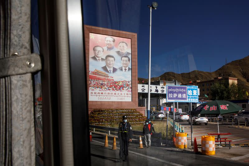 FILE PHOTO: A bus carrying foreign journalists on a government tour passes portraits of Chinese President Xin Jinping and former leaders at a checkpoint in Lhasa