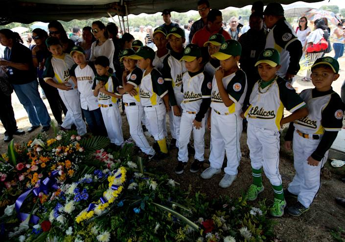 """In this photo taken on Friday, March 14, 2014. Boys that play in a minor league baseball team """"Atleticos de Crimon"""" mourn their coach, Guillermo Sanchez after his funeral grave in in Valencia, Venezuela. The people of the poor district of La Isabelica were made to pay for taking to the streets in anti-government protests. More than a dozen masked men on motorcycles roared through, shooting up a barricade and killing a university student and a 42-year-old man painting his house. (AP Photo/Fernando Llano)"""
