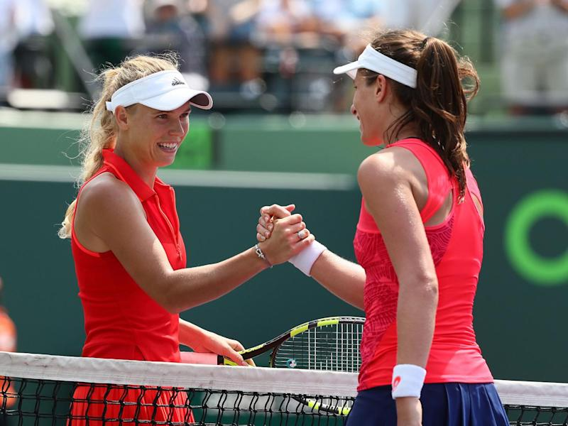 Konta meets Caroline Wozniacki at the net after securing victory (Getty)