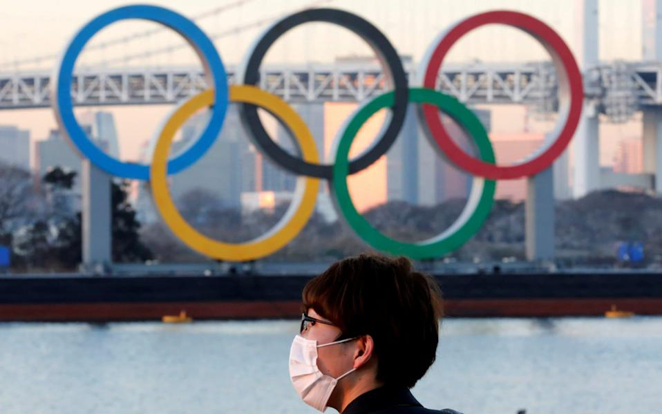 A man wears a protective mask amid the coronavirus disease (COVID-19) outbreak, in front of giant Olympic rings in Tokyo - Reuters