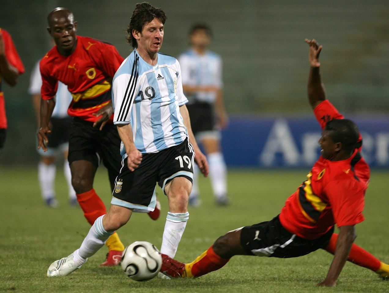 """FILE - In this May 30, 2006, file photo, Argentina's Lionel Messi dribbles past an unidentified Angola player during an exhibition soccer match in Salerno, Italy. In Spain, young soccer players can sign professional contracts when they turn 16, the minimum work age stipulated by Spanish law. Before that, children join training academies run by soccer clubs that field youth teams in amateur leagues. The most well-known example in Spain is Barcelona's """"La Masia"""" academy, where Lionel Messi started training at the age of 13 when his family emigrated from Argentina.  (AP Photo/Francesco Pecoraro, File)"""