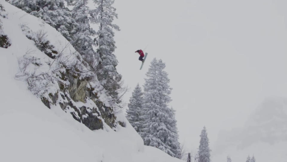 A skier leaping off a snowy rock face, in midair, two dozen feet above the snow beneath him.