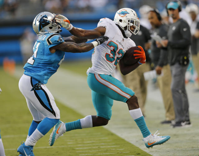 Miami Dolphins' Kenyan Drake (32) is knocked out of bounds by Carolina Panthers' Captain Munnerlyn (41) in the first half of a preseason NFL football game in Charlotte, N.C., Friday, Aug. 17, 2018. (AP Photo/Nell Redmond)
