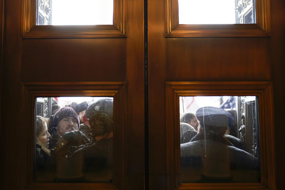 FILE - In this Jan 6, 2021, file photo, U.S. Capitol Police try to hold back rioters outside the east doors to the House side of the U.S. Capitol. At least a dozen of the 400 people charged so far in the Jan. 6 insurrection have made dubious claims about their encounters with officers at the Capitol. (AP Photo/Andrew Harnik, File)
