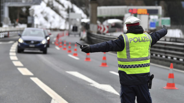An Austrian police officers stops a car coming from Italy on the autobahn near Gries am Brenner (AP)