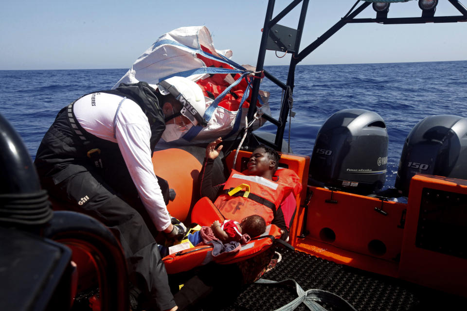 Rescuers from the MV Geo Barents vessel of MSF (Doctors Without Borders) assist a woman and infant, in the Mediterranean Sea, off Libya, in the central Mediterranean route, Monday, Sept. 20, 2021. (AP Photo/Ahmed Hatem)