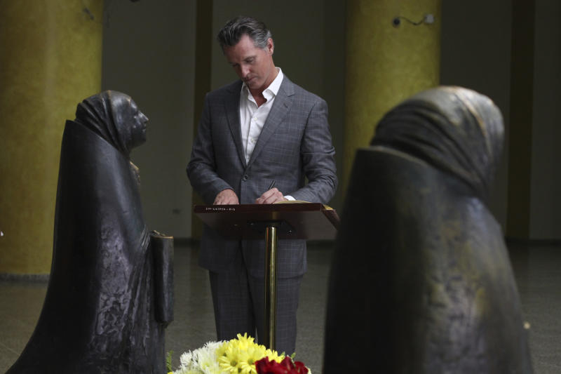 California Gov. Gavin Newsom writes a note on a book at the the tomb of Archbishop Oscar Romero at Metropolitan Cathedral in San Salvador, El Salvador, Sunday, April 7, 2019. Newsom visited the tomb of Archbishop Romero, the Salvadoran priest assassinated in 1980 due to his advocacy for human rights and the poor. (AP Photo/Salvador Melendez, Pool)