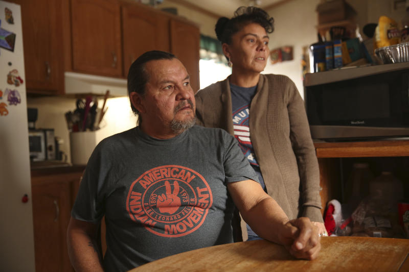 In this Dec. 11, 2019 photo, Henry Red Cloud, and Gloria Red Cloud, look out the window of their home on the Pine Ridge Indian Reservation in South Dakota. They fear what winter storms will do after flooding damaged their home last spring. They ran workshops on solar panel and wind turbine installation, but had to halt the classes when flooding damaged their tools and property. (AP Photo/Stephen Groves)