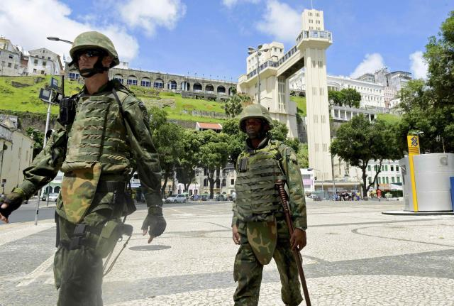 Soldiers patrol the city center during a police strike in Salvador, Bahia state, April 17, 2014. A police strike has unleashed violent crime in Brazil's third-largest city just two months before it is set to welcome hordes of soccer fans for the World Cup, adding to fears about the country's ability to ensure safety during the event. At least 22 people were killed in and around the northeastern city of Salvador after state police went on strike early on Wednesday to demand better pay and other benefits, the Bahia state government said on Thursday, prompting the federal government to dispatch troops to restore order. REUTERS/Valter Pontes (BRAZIL - Tags: CRIME LAW POLITICS CIVIL UNREST SPORT SOCCER WORLD CUP)