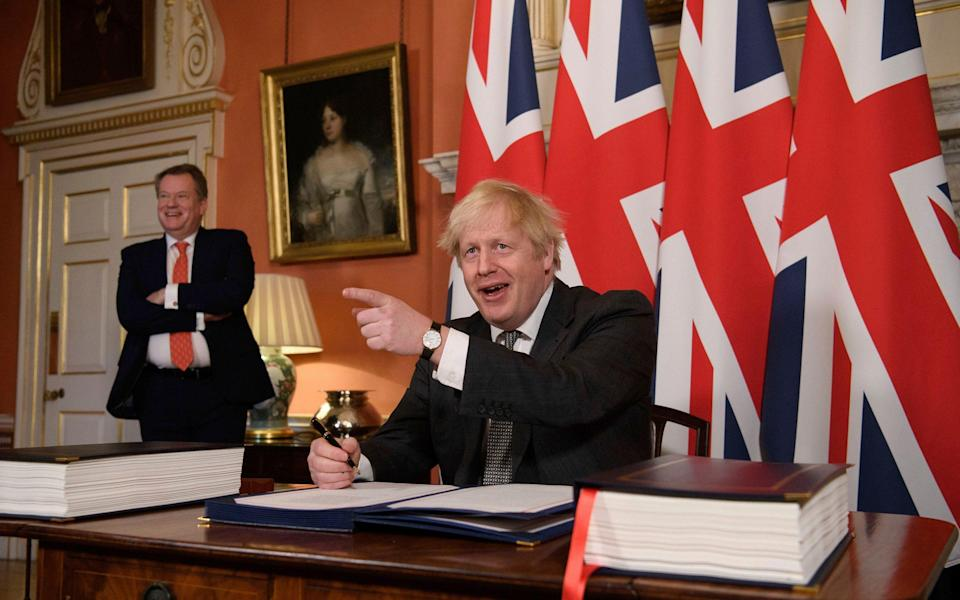 Lord Frost looks on as Boris Johnson signs the EU-UK Trade and Cooperation Agreement at Number 10 - Leon Neal/Getty