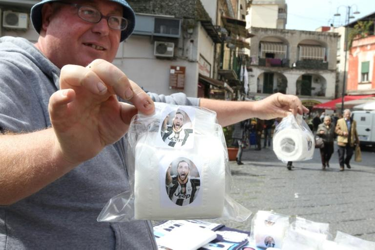A vendor shows toilet paper rolls with portraits of Juventus' Argentinian forward Gonzalo Higuain on March 23, 2017 in a street of Naples