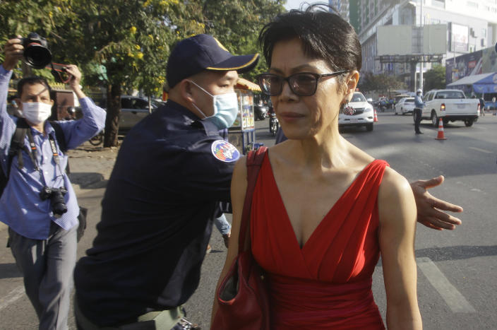 Theary Seng, right, a Cambodian-American lawyer, talks as she walks in front of Phnom Penh Municipal Court in Phnom Penh, Cambodia, Thursday, Jan. 14, 2021. Theary Seng said Thursday she was being persecuted for her political opinion as she and dozens of other government critics charged with treason and other offenses returned to court in a trial criticized by rights advocates. (AP Photo/Heng Sinith)