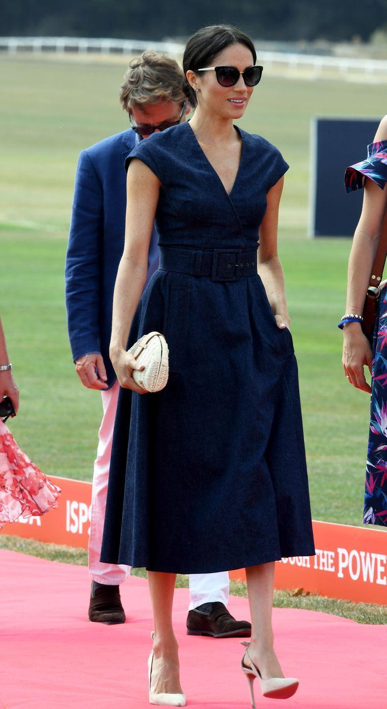 """<p>To show her support for Prince Harry at the <span class=""""redactor-unlink"""">Sentebale ISPS Handa Polo Cup</span>, Meghan wore a V-neckline denim midi dress by Carolina Herrera with a belt that cinched in her waist. </p><p>The 36-year-old accessorised her look with a <span class=""""redactor-unlink"""">basket clutch by J. Crew</span>, Tom Ford sunglasses, and her favourite <span class=""""redactor-unlink"""">Aquazzura Deneuve slingback heels. </span></p>"""