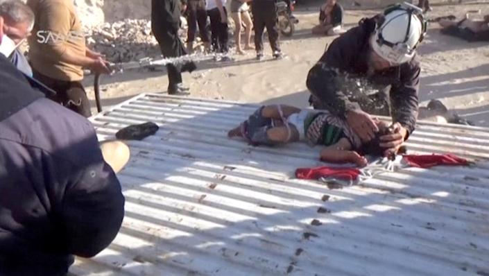 <p>A still image taken from a video posted to a social media website on April 4, 2017, shows a civil defense member helping a child who is being sprayed with water, said to be in the town of Khan Sheikhoun, after what rescue workers described as a suspected gas attack in rebel-held Idlib, Syria. (Social Media Website via Reuters TV) </p>
